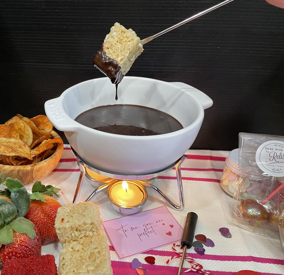 A white ceramic fondue pot is filled with rich chocolate sauce for dipping a variety of fun foods including the rice crispy treat that has just been dipped and is dripping chocolate in this photo of a fondue kit created for home use.