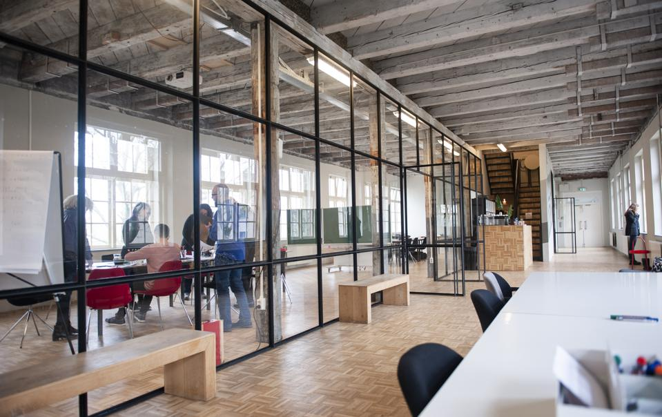 A team is working behind glass in a large modern office space
