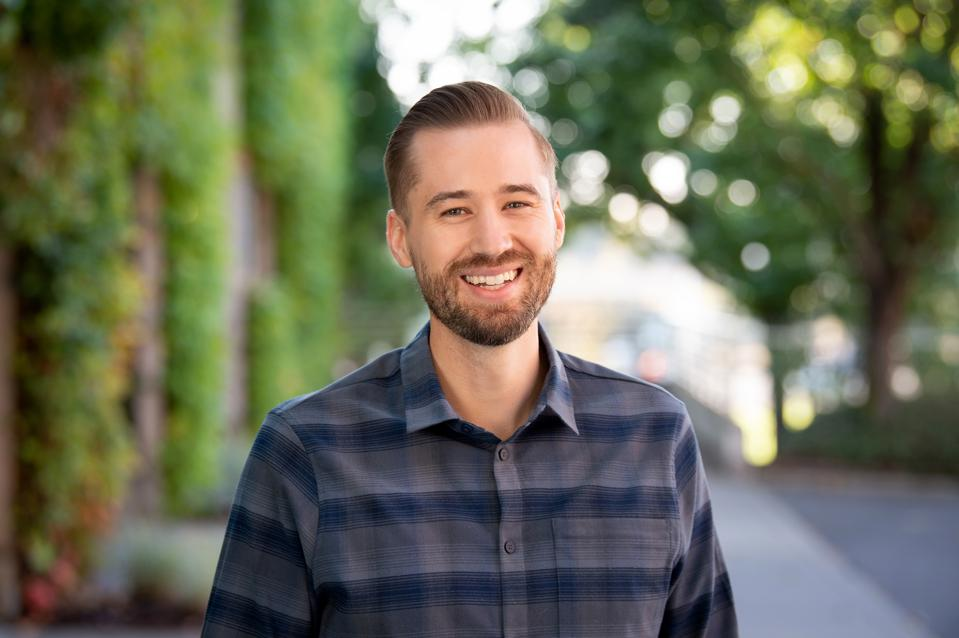 A young white man with beard wearing a plaid shirt smiling into camera