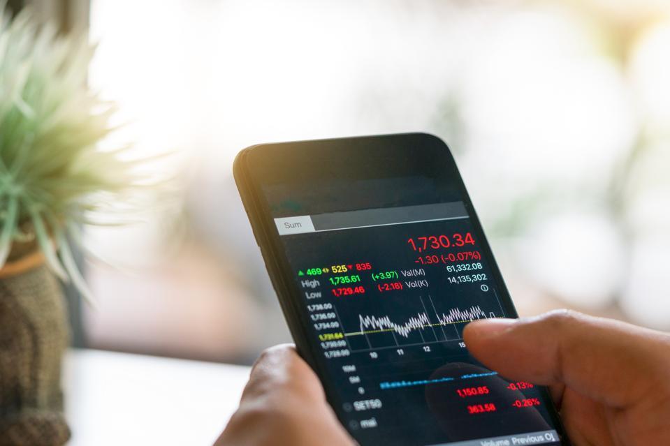 Businessman trading stocks with smarthphone