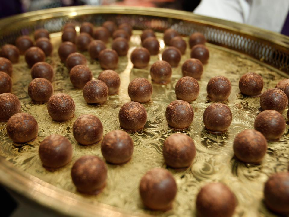 A gold platter dotted with chocolate truffles