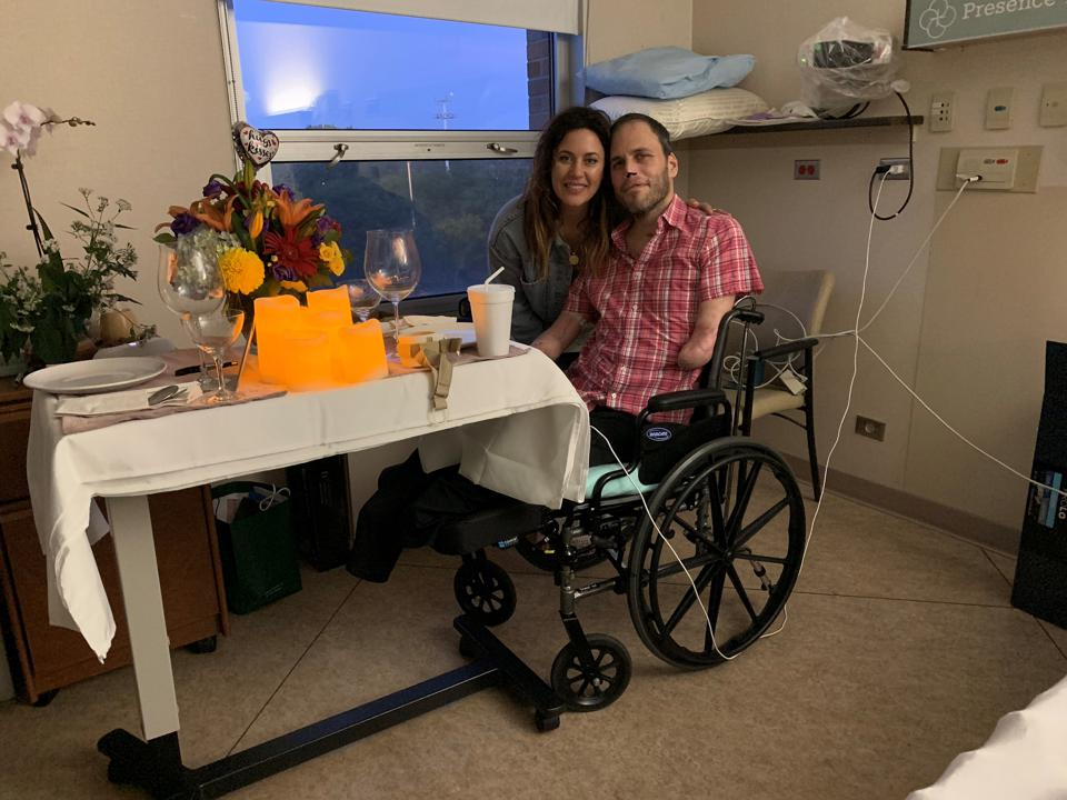Jason Markoff in a wheelchair in a hospital with wife beside him. He has no legs or arms.