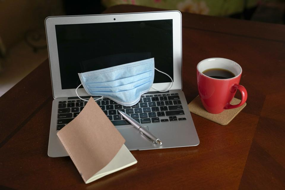 Face mask on top of laptop. Quarantine and self isolation. Stay and work at home.