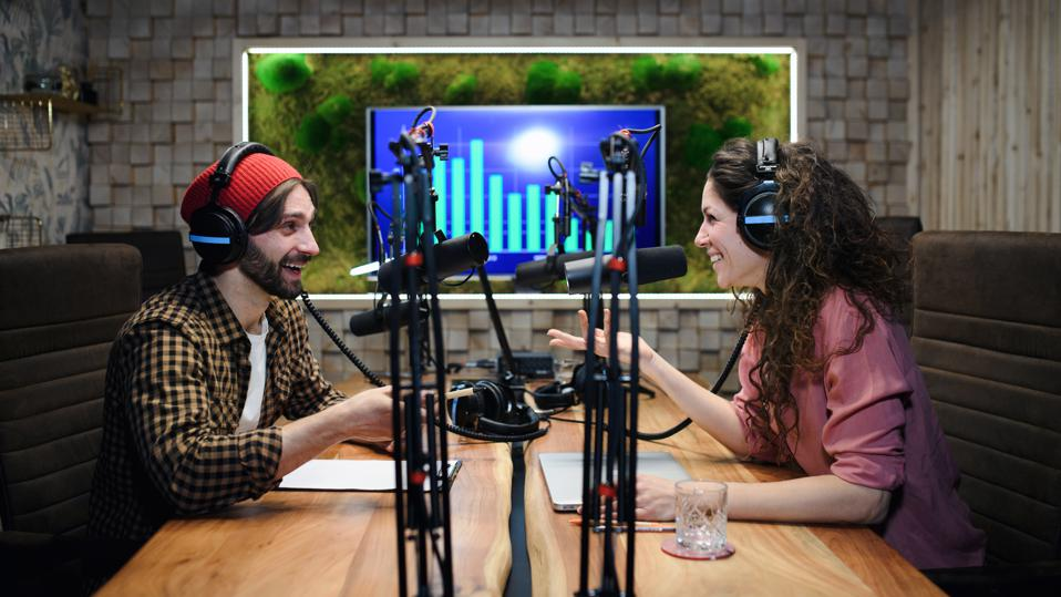 Young woman and man makes a podcast audio recording in a studio.