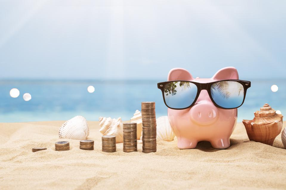 A sunny beach with coins and shells in the sand and a piggy bank wearing sunglasses.