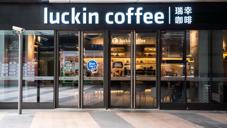 Chinese coffee shop chain Luckin Coffee logo and store seen...