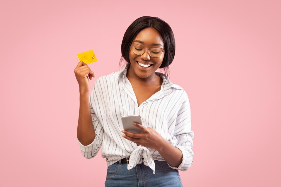 Afro Girl Using Cellphone And Credit Card Standing, Studio Shot
