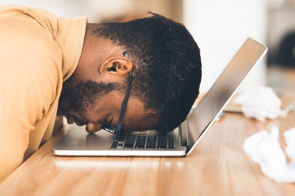 Homeworker with head on computer