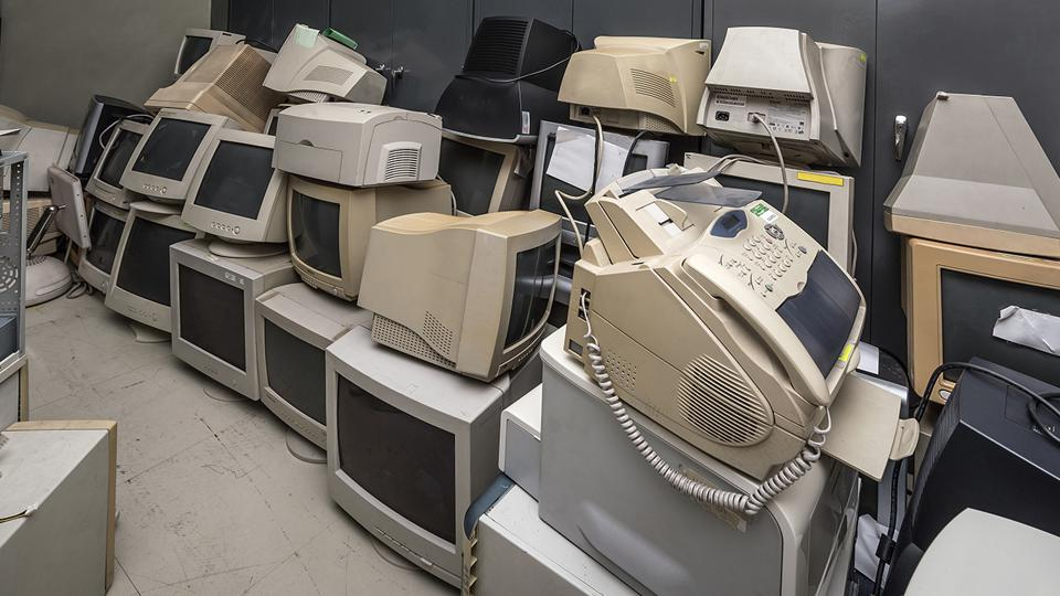 Very old computer equipment and fax machines are stacked high in a room.