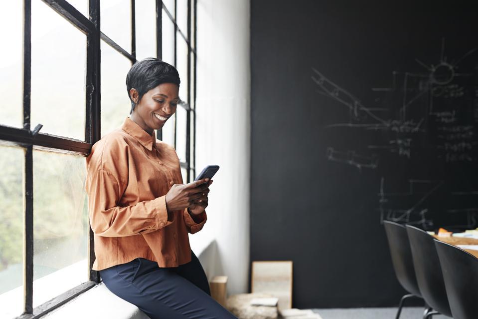 Smiling entrepreneur using phone in office meeting
