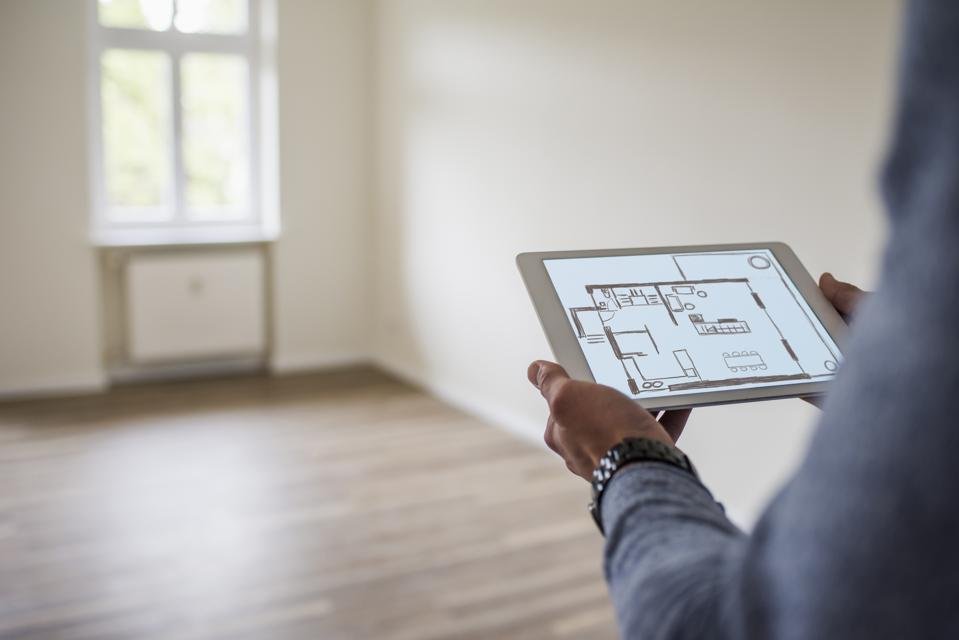 Man in new home holding tablet with floor plan