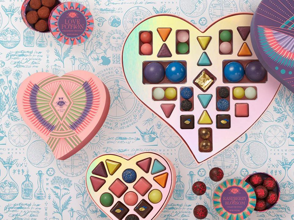 A heart-shaped purple box filled w chocolates in many different colors and shapes