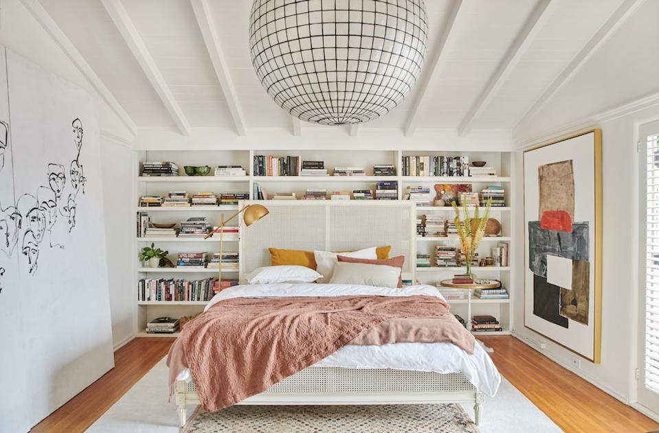 An airy bedroom with a bookshelf and art.