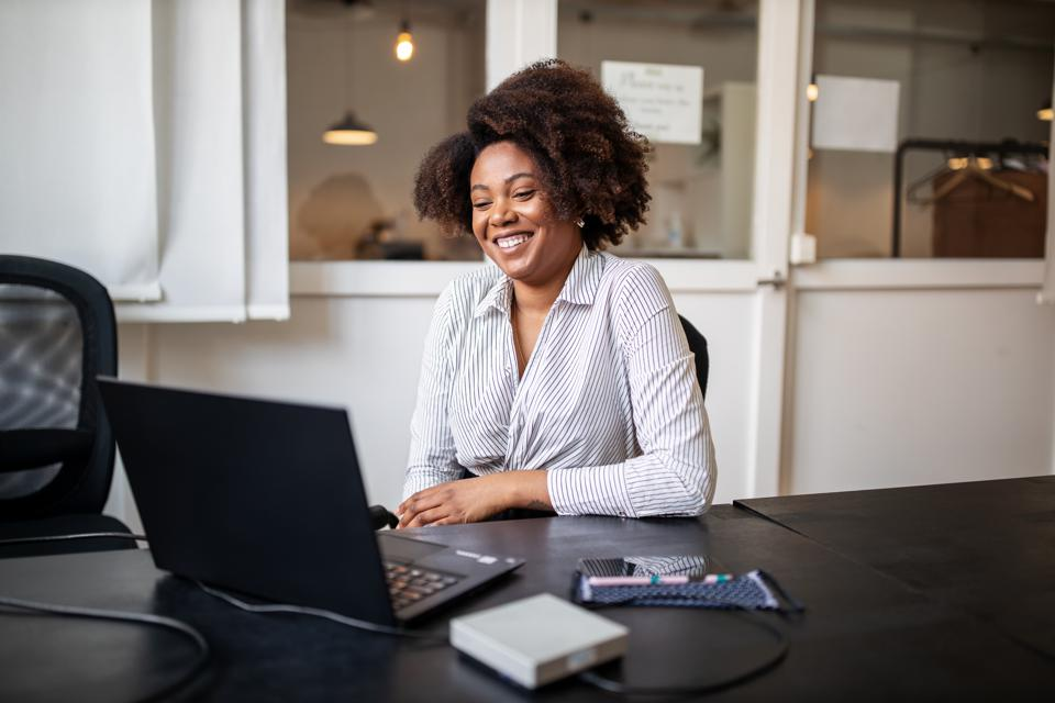Businesswoman sitting in office smiling during a video call