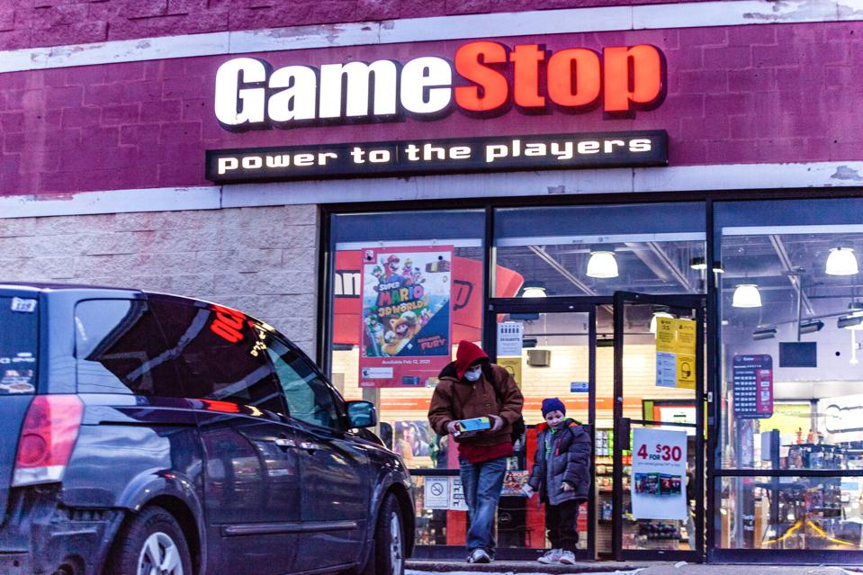 Man and child wearing face masks leave Gamestop store.