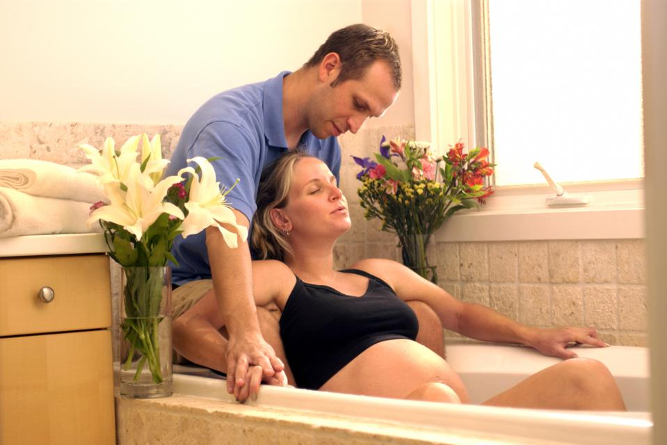 Expecting couple in bathtub for water birth