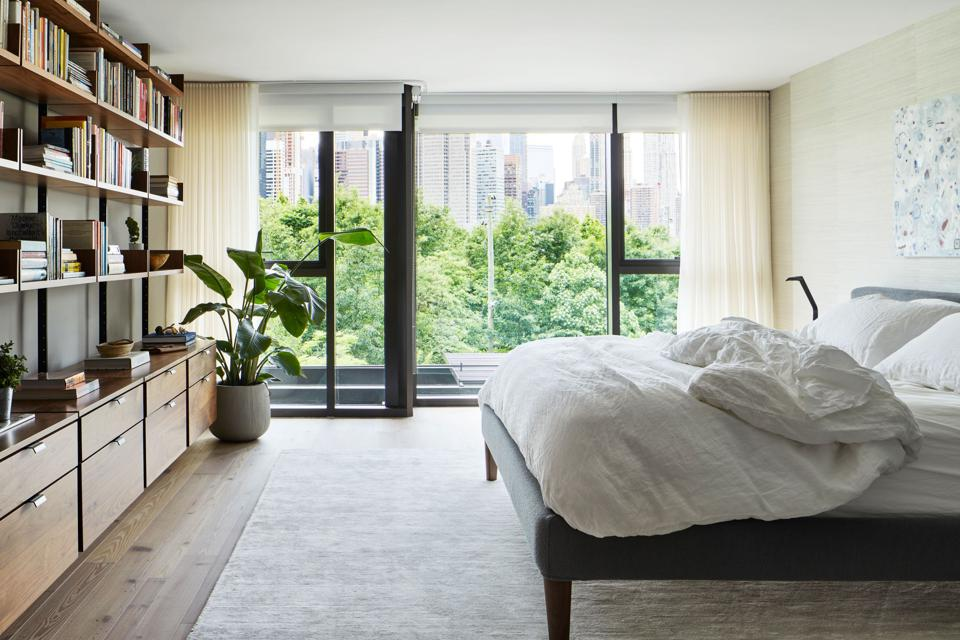 Spacious bedroom with plant, bookcase and organic bedding.