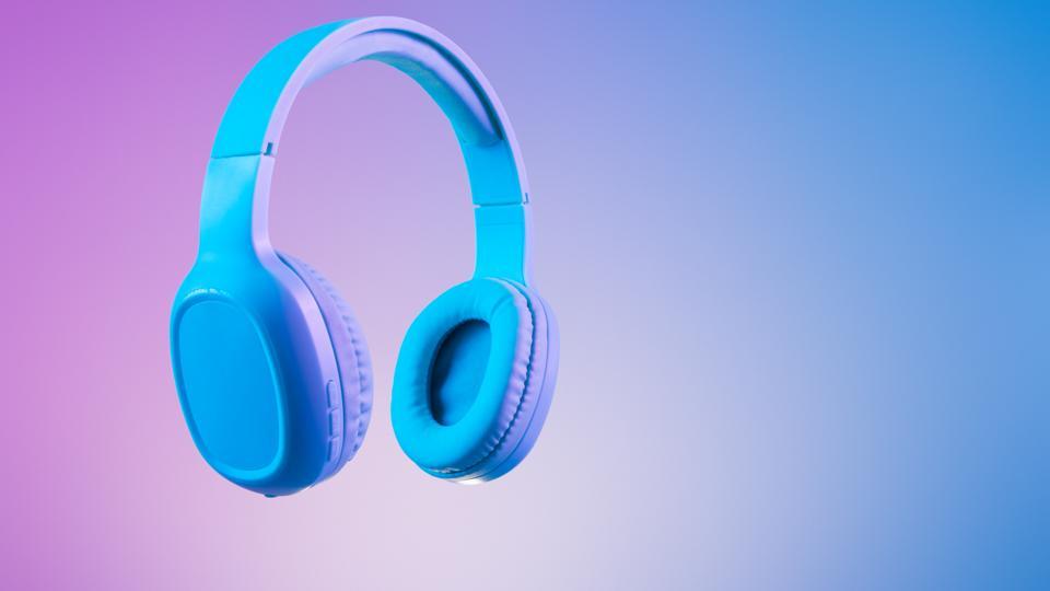 Stylish blue headphones on multi colored / duo tone background lighting