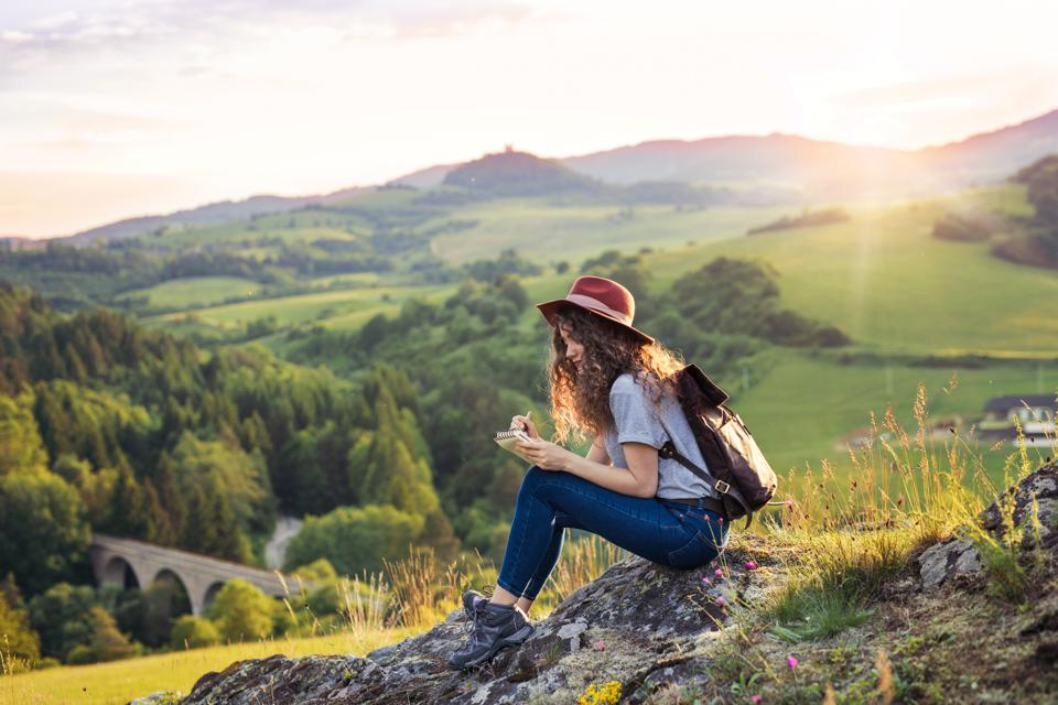 Young tourist woman traveller with backpack sitting in nature, writing notes.