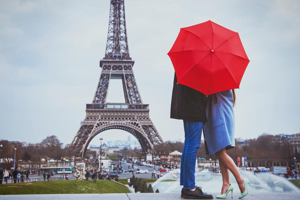 Couple kissing under umbrella at the Eiffel Tower
