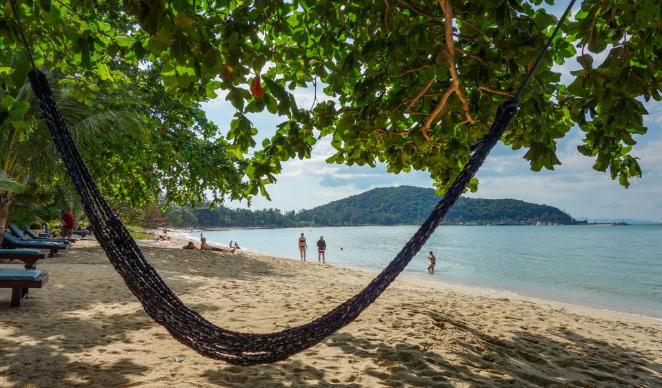 A empty hammock is stretched over a quiet beach Koh Samui, Thailand, in the winter