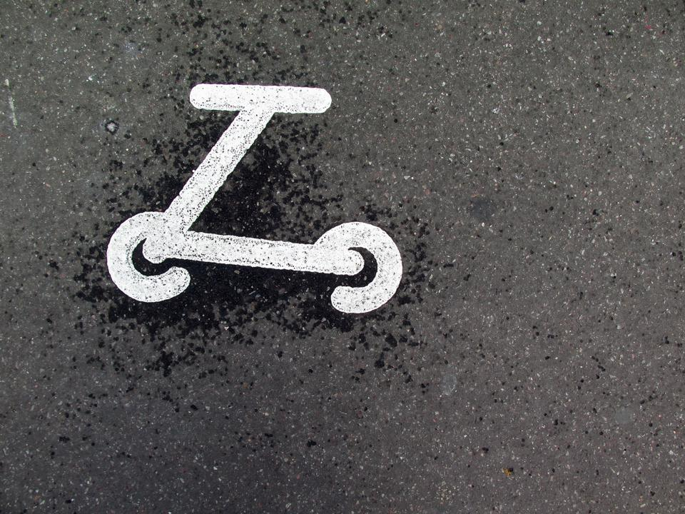 The logo of a painted scooter on an asphalt street in Paris