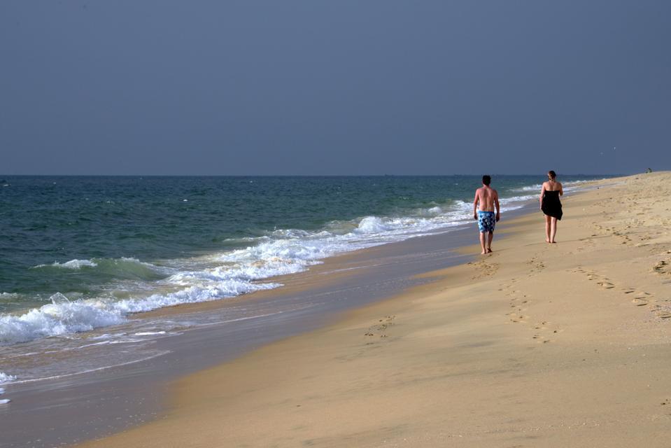 Los turistas caminan por la playa de Marari en Karala, India en enero