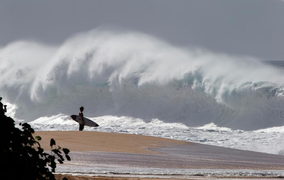 A surfer watches big waves at Banzai Pipeline  on the north shore of Oahu in Hawaii
