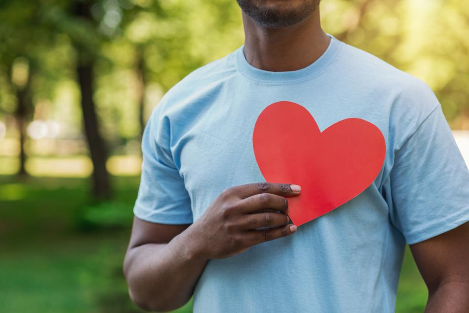 Black man holding red heart on his chest