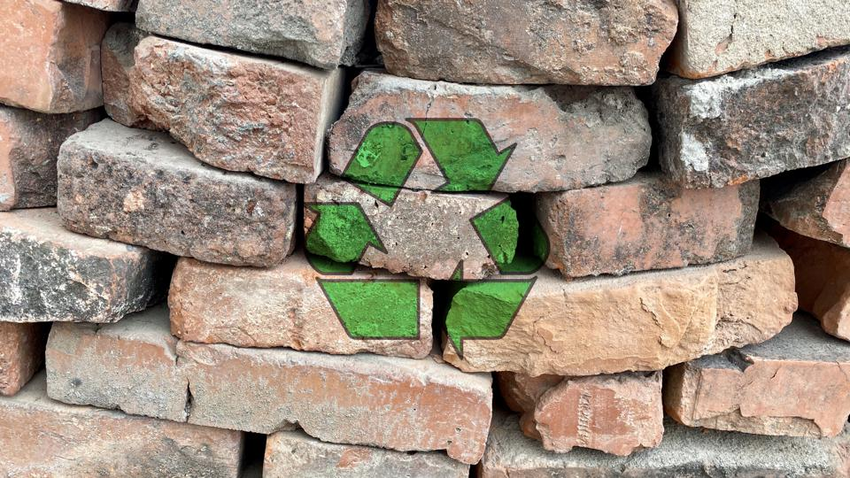 Recycling icon on a pile of red bricks from a construction site, sort and recycle waste building materials