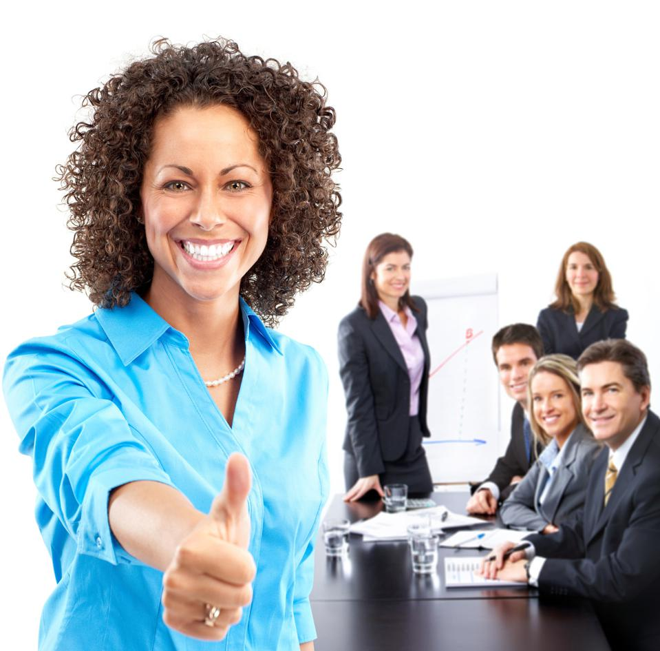 Businesswoman giving thumbs-up with her team behind her.