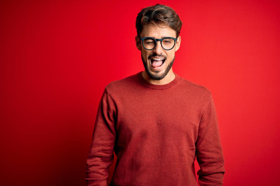 Young handsome man with beard wearing glasses and sweater standing over red background winking looking at the camera with sexy expression, cheerful and happy face.