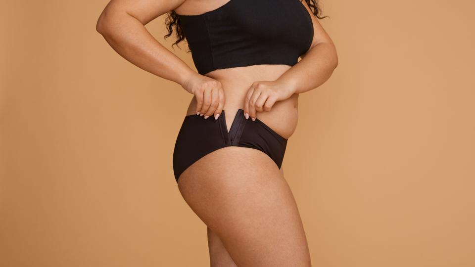 A woman attaches side-fastening black underwear by Slick Chicks.