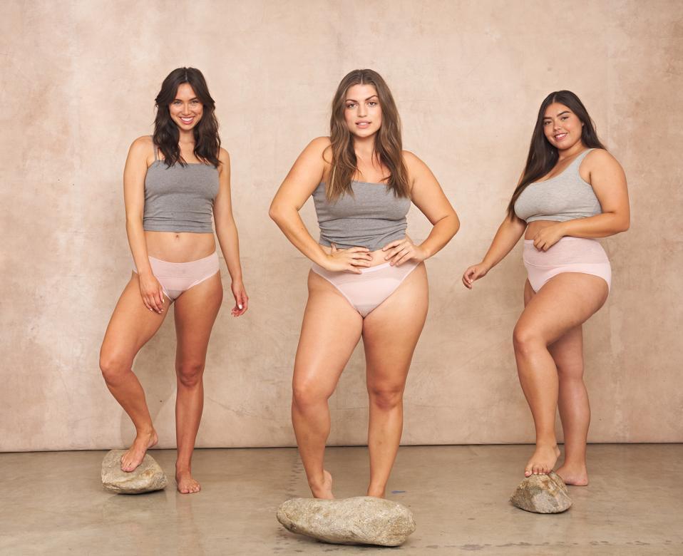 Three models stand on rocks wearing Saalt leakproof underwear in Quartz Blush.