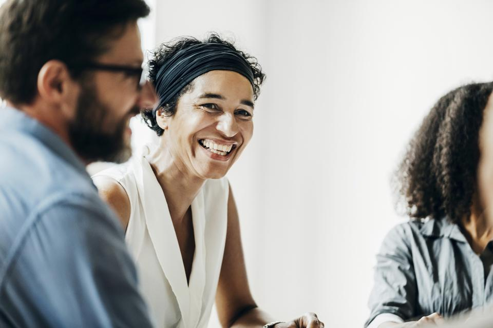 Woman Smiling While Talking With Office Colleagues
