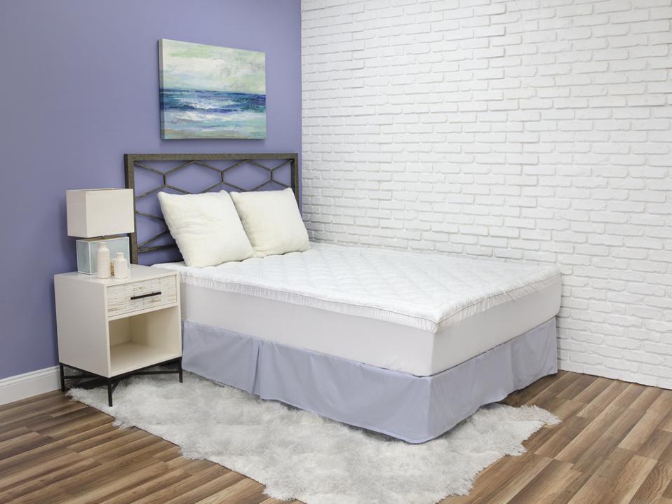 SensorPEDIC's hypoallergenic mattress pad on top of a mattress in a model room.