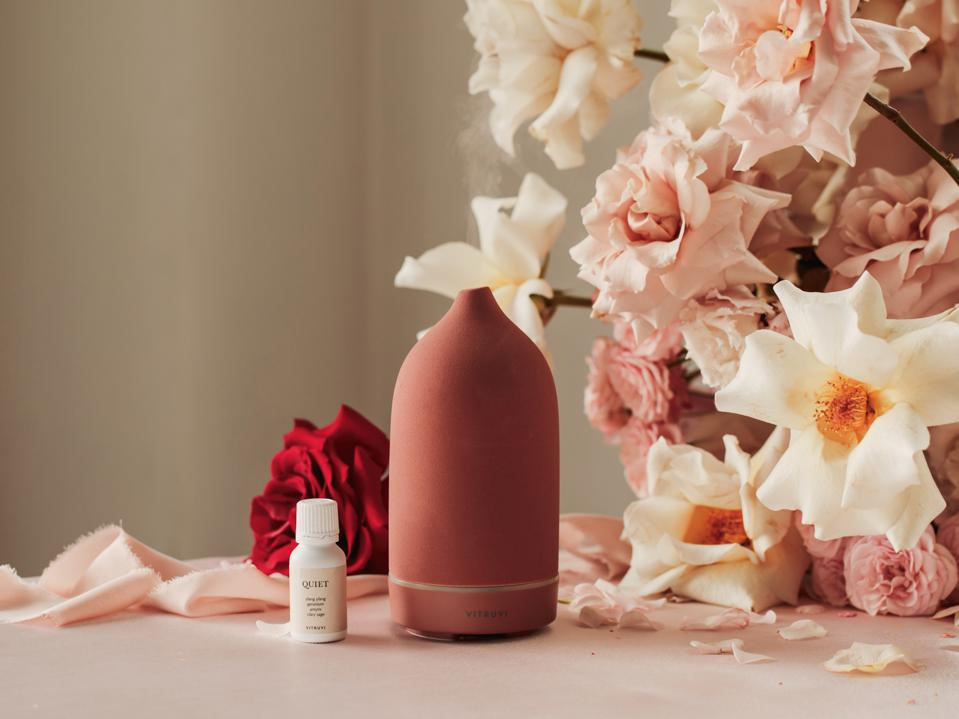 A Vitruvi rose stone diffuser next to an essential oil bottle and pink and white flowers.