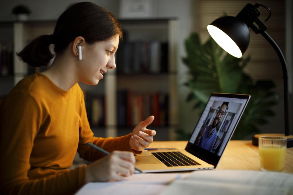 Smiling teenage girl with bluetooth headphones having video call on laptop computer at home
