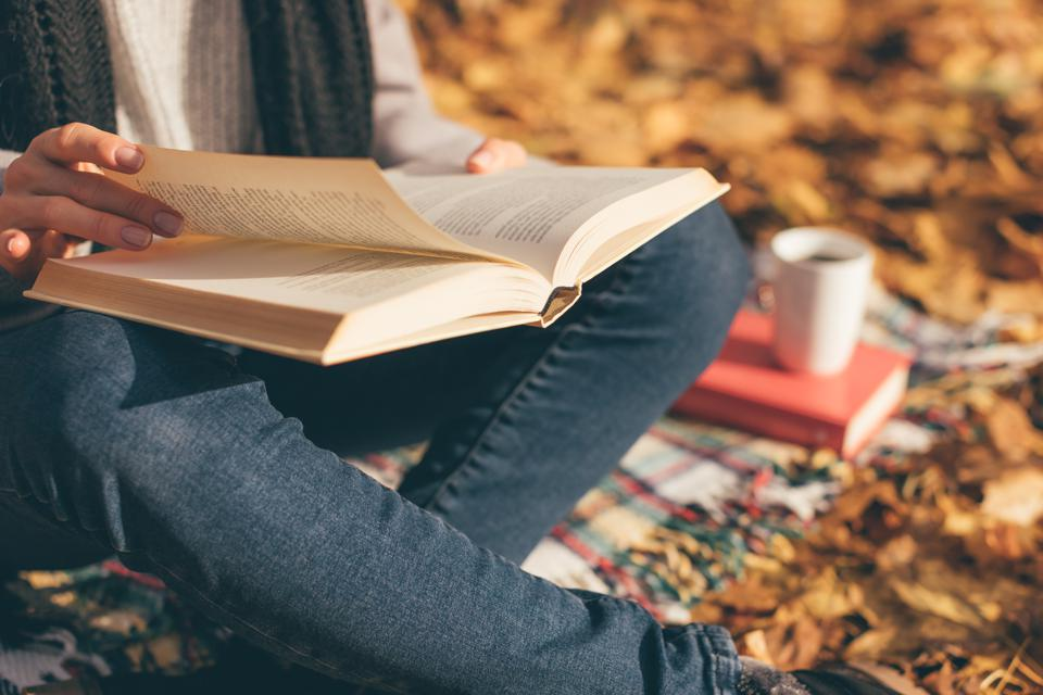 Woman reading a book with a coffee in autumn.