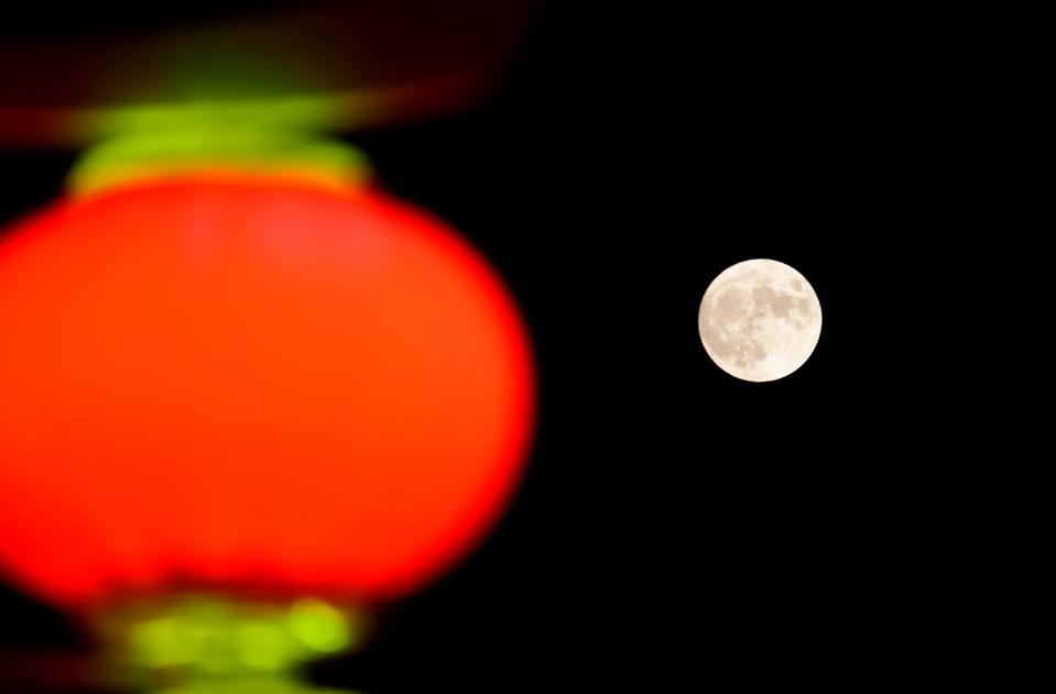 The full moon is seen behind a red lantern on Mid-Autumn Festival on October 1, 2020 in Shijiazhuang, Hebei Province of China. (Photo by Jia Minjie/VCG via Getty Images)