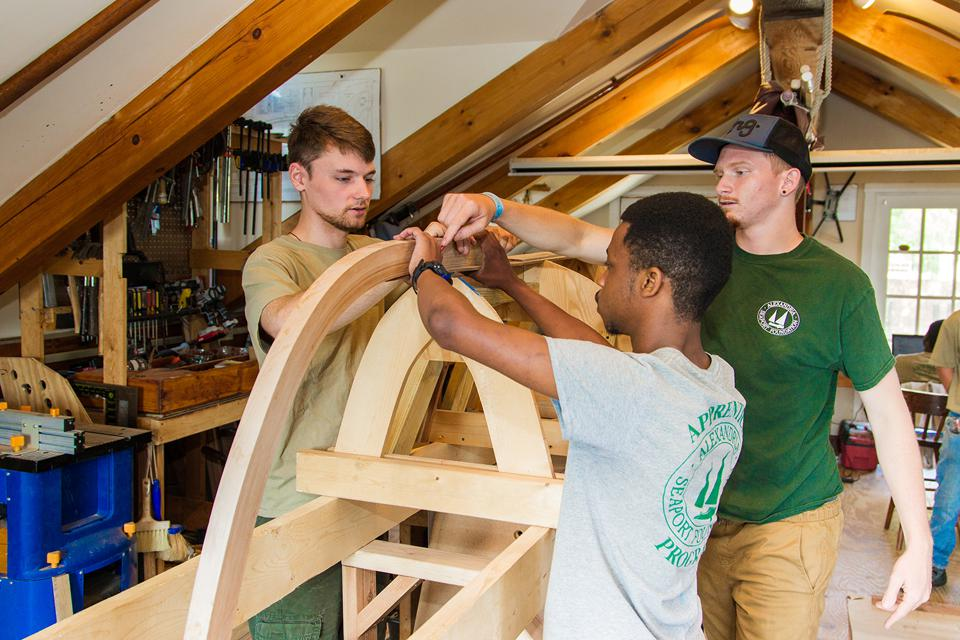Three male youth working together to build boat as part of community youth program.