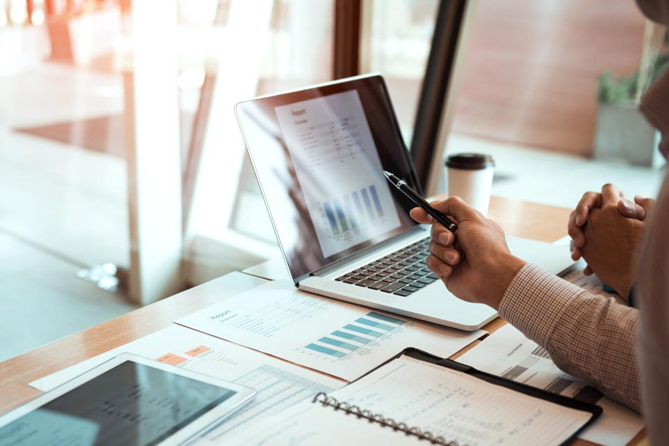 Businessperson analyzing financial data on desktop