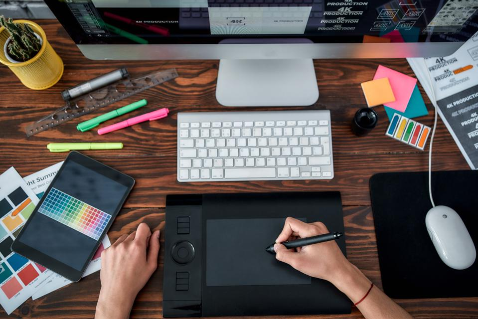 Design tools. Top view of a designer using graphic tablet and working with computer while sitting at his workplace in the office. Top view of a workplace with graphic tablet, keyboard and computer.