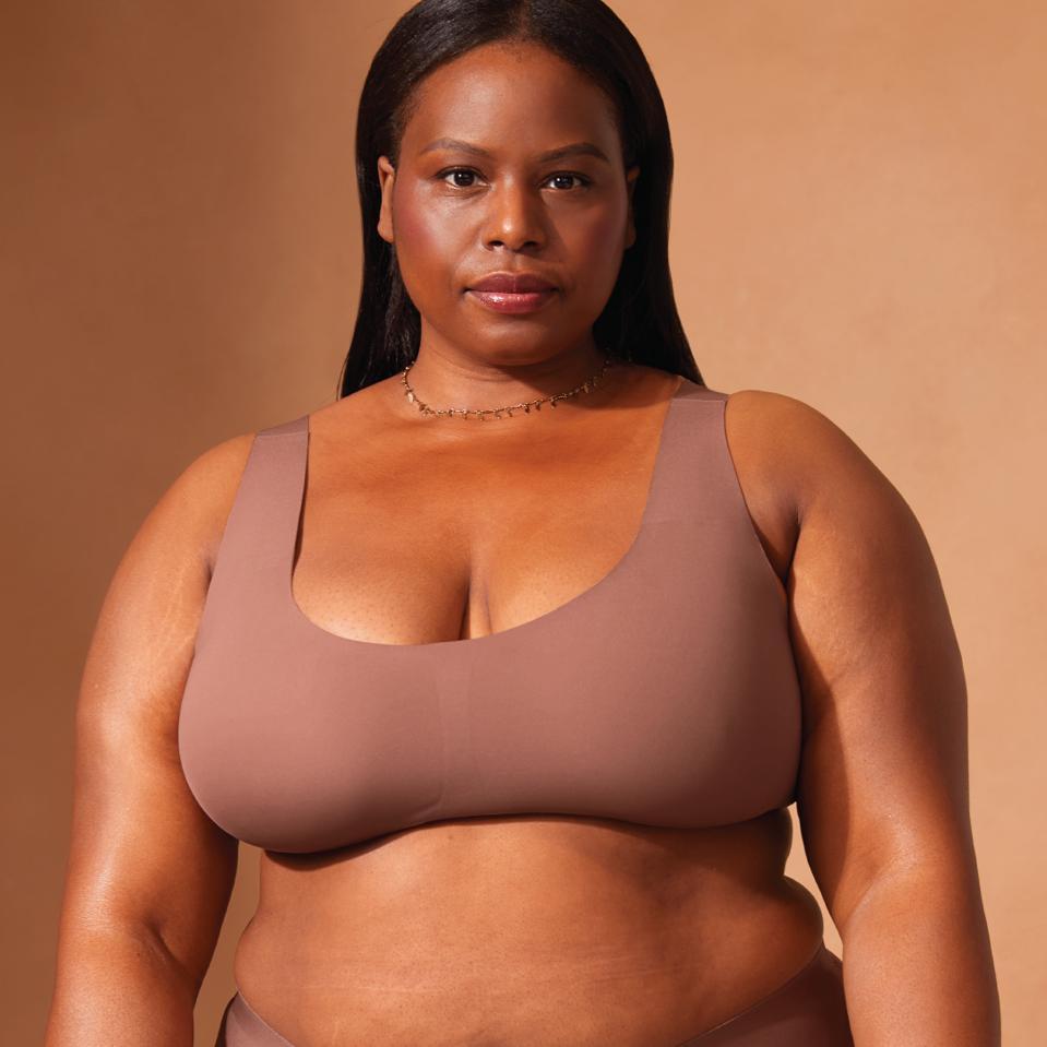 A black woman models a beige Knix bra against a brown background.