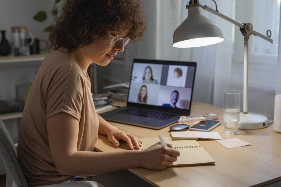 Working from Home During the Lockdown: a Happy Woman Attending a Business Meeting Through a Video Call on her Laptop Computer