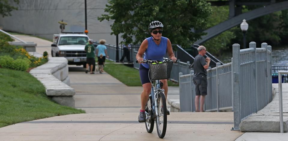 People walked and biked as landscaping crews put the finishing touches on the last, short link of the Rum River Regional Trail.