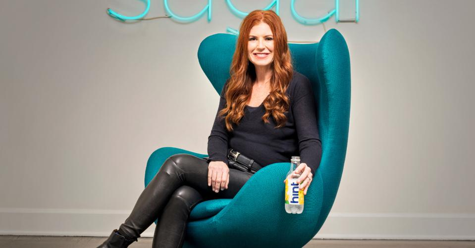 Kara Goldin sitting on on a chair with a Hint bottle.