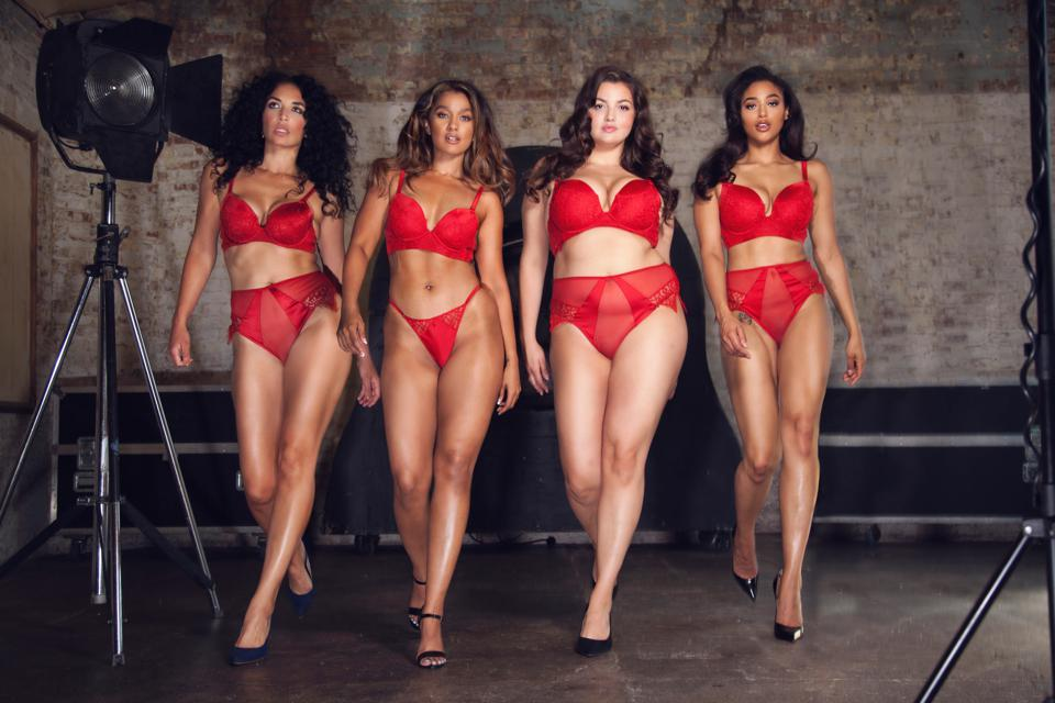 Four women of different sizes walk in red lingerie and black heels.