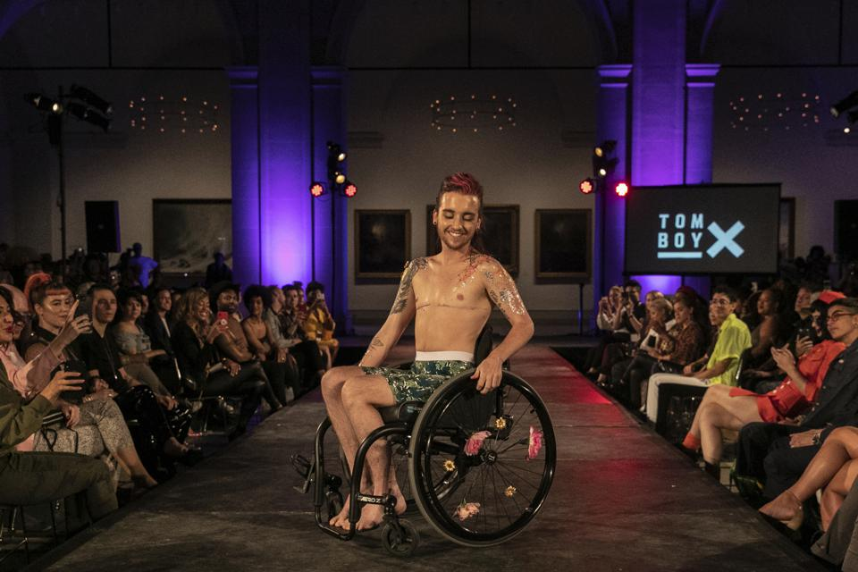A man in a wheelchair models TomboyX at the dapperQ Runway Show at the Brooklyn Museum.
