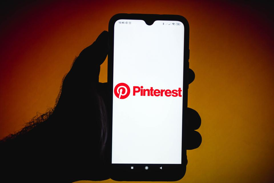 In this photo illustration the Pinterest logo seen displayed...